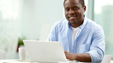 a smiling man using a laptop computer